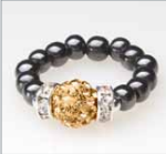 black beaded stretch ring with gold crystal accent bead